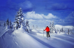 Skier skiing downhill in high mountains against sunset Stock Images