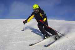 Skier skiing downhill in mountains Stock Images