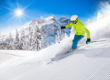 Skier skiing downhill in high mountains. Skier skiing downhill during sunny day in high mountains Royalty Free Stock Photos