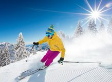 Skier skiing downhill in high mountains. Skier skiing downhill during sunny day in high mountains Royalty Free Stock Images