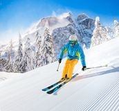 Skier skiing downhill in high mountains. Skier skiing downhill during sunny day in high mountains Stock Photos