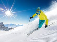 Skier skiing downhill in high mountains. Skier skiing downhill during sunny day in high mountains Stock Image