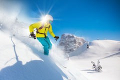 Skier skiing downhill in high mountains. During sunny day Royalty Free Stock Images
