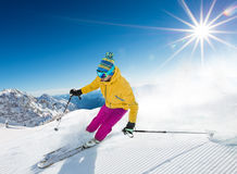 Skier skiing downhill in high mountains. Skier skiing downhill during sunny day in high mountains Royalty Free Stock Photography