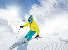Skier skiing downhill in high mountains. Skier skiing downhill during sunny day in high mountains Stock Photography