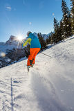 Skier skiing downhill in high mountains. Skier skiing downhill during sunny day in high mountains Royalty Free Stock Image