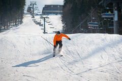 Skier skiing downhill after jumping at ski resort. Against ski-lift and snow slope. Man is wearing orange jacket, helmet and goggles. Carpathian Mountains Stock Photography