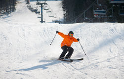 Skier skiing downhill in the moment of falling. At ski resort against ski-lift and snow slope. Man is wearing orange jacket, helmet and goggles. Carpathian Stock Photography