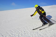 Skier skiing downhill in mountains Stock Photo