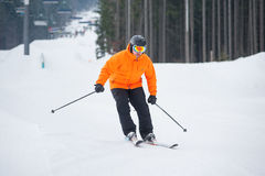 Skier skiing downhill at ski resort against ski-lift. And forest. Male is wearing orange jacket, helmet and goggles. Carpathian Mountains, Bukovel Royalty Free Stock Photo