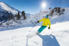 Skier skiing downhill in high mountains. Skier skiing downhill during sunny day in high mountains Royalty Free Stock Photo