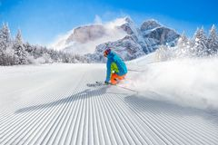 Skier skiing downhill in high mountains. Skier skiing downhill during sunny day in high mountains Stock Photo