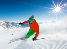 Skier skiing downhill in high mountains. Skier skiing downhill during sunny day in high mountains Stock Images