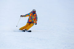Skier skiing in fresh snow on ski slope Royalty Free Stock Images