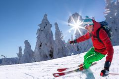 Skier skiing downhill in high mountains against blue sky Stock Photos