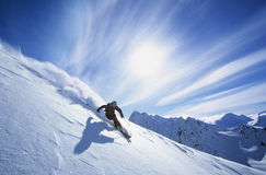 Skier Skiing On Mountain Slope. Full length of skier skiing on fresh powder snow stock photography