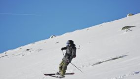 Skier Skiing Mountain Winter Snow Slowmotion. Slowmotion footage of a skier riding down the mountain stock video footage