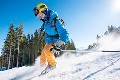Skier skiing in the mountains. Male skier skiing on fresh snow in the mountains on a sunny beautiful day extreme fun happiness activity lifestyle concept Stock Photography