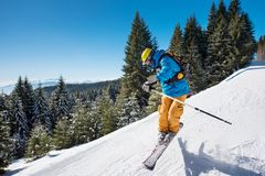 Skier skiing in the mountains. Shot of a skier jumping in the air while riding down the slope in the mountains on a sunny winter day copyspace adrenaline extreme Royalty Free Stock Photo