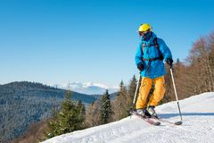 Skier skiing in the mountains. Shot of a professional skier in colorful gear skiing on fresh powder snow in the mountains on the winter resort. Blue sky and Royalty Free Stock Photos