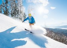 Skier skiing in the mountains. Shot of a professional skier skiing in the mountains on fresh powder snow on a beautiful sunny winter day on the winter resort Royalty Free Stock Image