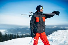 Skier with skis and poles in hands, winter sport. Skier poses with skis and poles in hands, blue sky and snowy mountains on background. Winter active sport Stock Photos