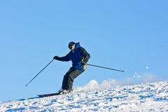Skier on the slope. Over the sky. You can delete sky and it would be an isolated image. It can be called isolated over blue sky Royalty Free Stock Photography