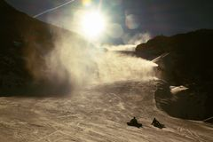Skier in slope. A snowgun makes fresh powder snow. Snow making on slope. Mountain ski resort and winter calm. Stock Photo