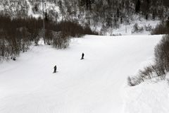 Skier and snowboarder downhill on ski slope at gray winter day Stock Photo