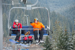 Skier and snowboarder riding up on ski lift Stock Photos