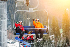 Skier and snowboarder riding up on ski lift Stock Photography