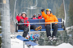 Skier and snowboarder riding up on ski lift Stock Photo