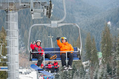 Skier and snowboarder riding up on ski lift Royalty Free Stock Photos
