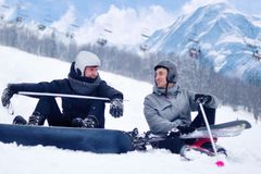 Skier and snowboarder after skiing and snowboarding rest, sit talk, laugh against the background of mountains. Skiing and snowboar stock photo