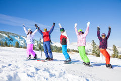 Skier and snowboarders in a row lifting hands up Stock Photo