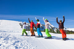Skier and snowboarders in a row lifting hands up Royalty Free Stock Photo