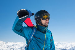 Skier at snowy mountain. Pensive skier carrying ski on shoulders on the peak of the snowy mountain. Portrait of young thoughtful man looking snowy panorama stock photography