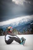 Skier in snowy mountains. Male skier with ski fastenings sat under dark clouds on snowy mountain stock photos