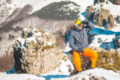 Skier sportsman at mountain cliff with a panoramic background Stock Photos