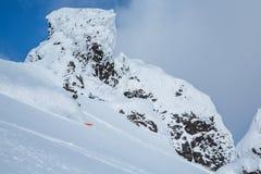 Skier spraying soft powdery snow among volcanic peak in the backcountry near Niseko, Japan. On the island of Hokkaido, a skier slashes through soft powder snow stock photo