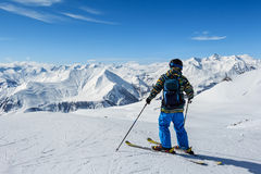 Skier standing in front of mountains Royalty Free Stock Photo