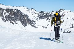 Skier standing on a hill overlooking large cliffs and couloirs above hte Snowbird Glacier of the Alaska backcountry. Backcountry skier overlooking large cliff stock photography