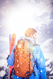Skier standing with ski on snow covered mountains royalty free stock image