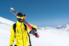 Skier standing on a slope. Man in a light suit, the helmet and mask in skiing is to ski. In the background snow-capped. Mountains , skiers . Caucasus Mountains royalty free stock photo