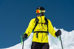 Skier standing on a slope. Man in a light suit, the helmet and mask in skiing is to ski. In the background snow-capped. Mountains , skiers . Caucasus Mountains stock photo