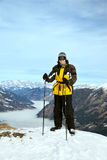 The skier stands on mountain summit. Against heavy fog stock images