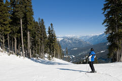 Skier stopped on trail, looking at mountains Royalty Free Stock Image