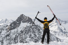 Skier success. Skier raises his gear in the air as sign of success after reaching the summit Royalty Free Stock Photos