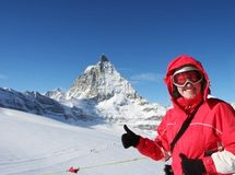 Skier in Swiss Alps. Smiling woman on the sunny slope of Swiss Alps over gigantic peak Matterhorn Royalty Free Stock Photo