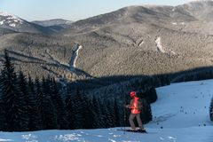 Skier at the top of descent enjoying mountains and forests. Rear view of male skier with a backpack is at the top of the descent enjoying the scenery of local Royalty Free Stock Photography